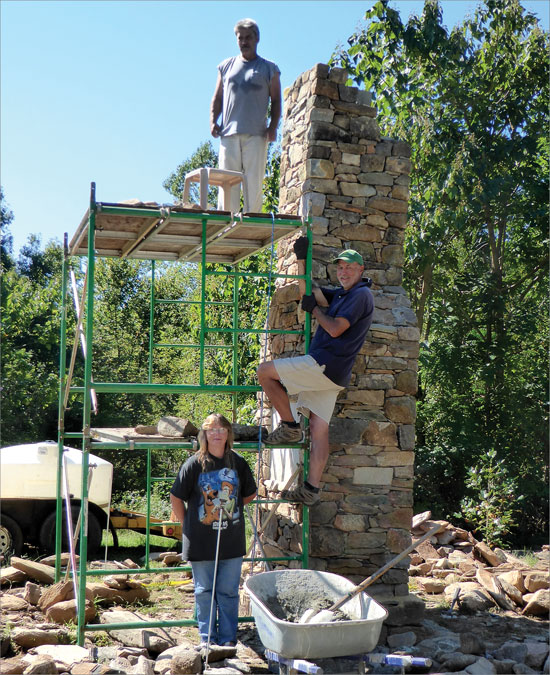 From top to bottom: Darryl Whidby, Larry Lamb, and Jackie Whidby.  The chimney as it neared completion on one of many scorching hot days.